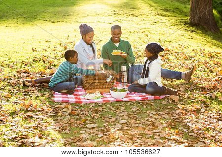Happy family picnicking in the park together on an autumns day