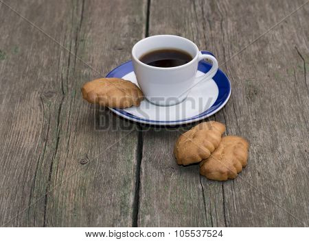 Cup Of Coffee And Some Cookies On A Wooden Table