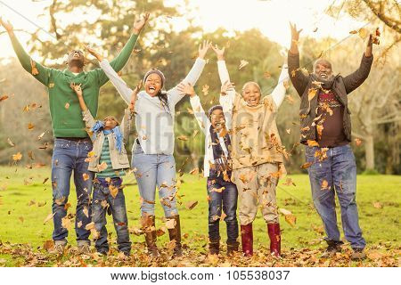 Happy family throwing leaves around in parkland