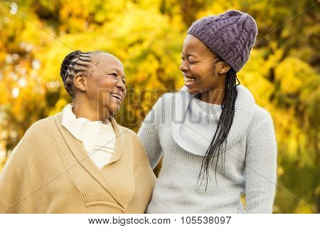 Mother and grandmother smiling to each other in parkland