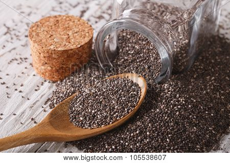 Chia Seeds Are Poured Out From A Jar And Spoon Close-up. Horizontal