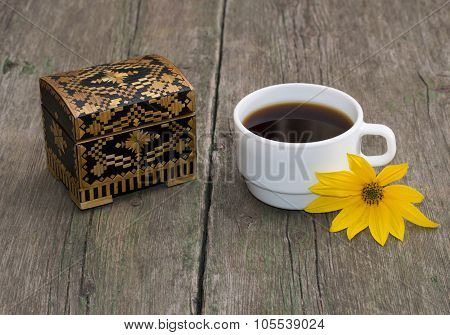 The Cup Of Coffee Decorated With A Yellow Flower And Casket, Still Life