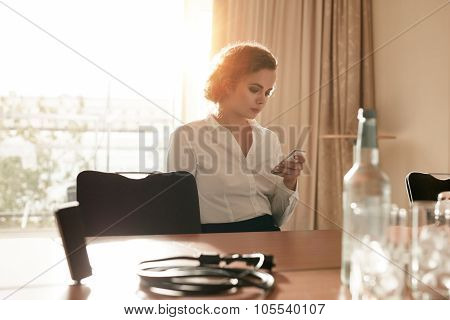 Businesswoman At Conference Table Using Mobile Phone