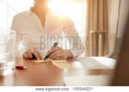 Woman Writing On Sticky Notes At Conference Room
