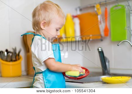 Child washing dishes in a domestic kitchen