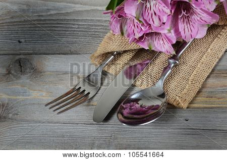 Tableware with flowers on wooden background close up