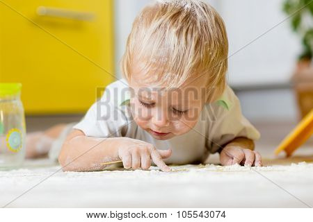 Little child laying on very messy kitchen floor, covered in white baking flour