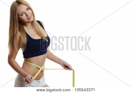 Sporty girl measuring her weist with tape on white background