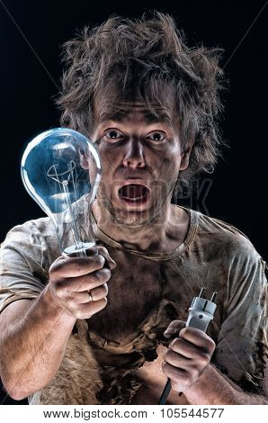 Portrait of burnt man with light bulb and electric plug over black background