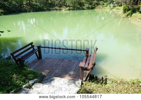Wooden Seat On The Pier And The Fish In The Pond
