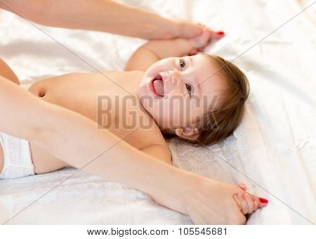 Baby massage. Mother massaging and doing gymnastic to kid