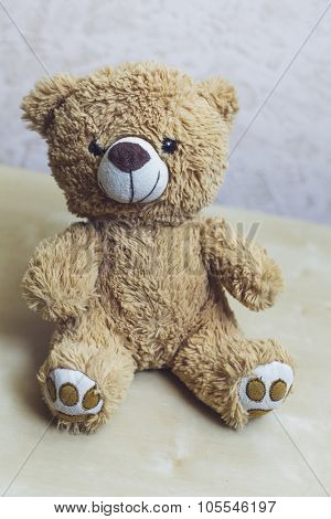 Old patched brown teddy bear