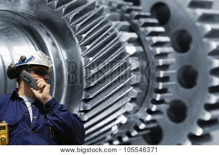 engineer, worker with gears and axles machiney in background, metal bluish toning concept