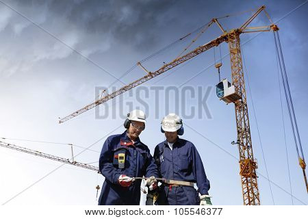 two workers inside building-site, cranes and scaffolding