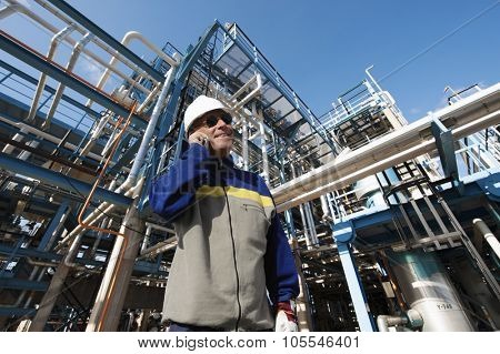 oil worker talking in phone with refinery pipelines in background