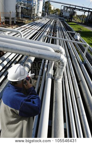oil worker pointing out on long stretched pipelines inside refinery industry