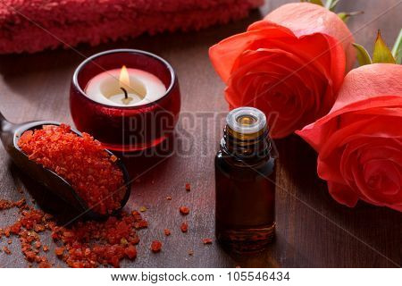 Mineral bath salts, Essential oil, candle and flowers on the brown wooden table.