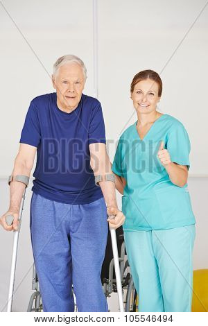 Physiotherapist holding thumbs up next to senior man with crutches