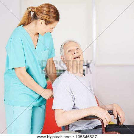 Old disbabled man sitting in wheelchair driven by a geratric nurse