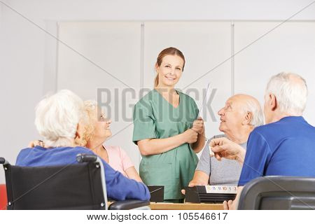 Smiling female geratric nurse standing with a group of senior people