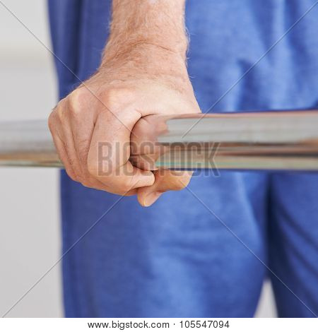 Old hand of senior man holding on to handle of a treadmill
