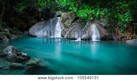 Jangle landscape with flowing turquoise water of Erawan cascade waterfall. Kanchanaburi, Thailand
