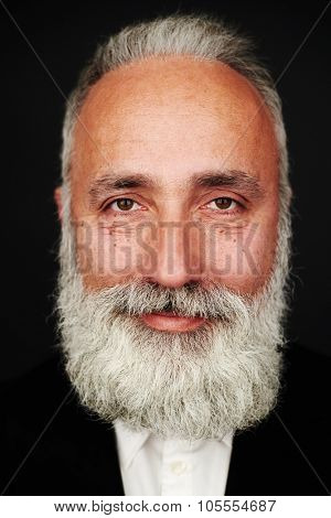 portrait of smiley bearded senior man in formal wear over black background
