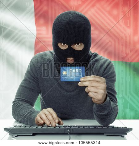 Dark-skinned Hacker With Flag On Background Holding Credit Card - Madagascar