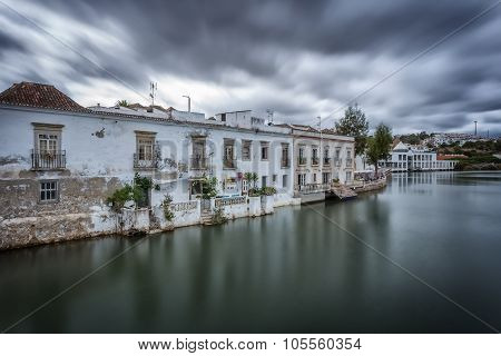 A Dramatic Urban Landscape Of Ancient Houses On The River. Tavira, Portugal.