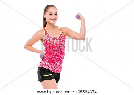 Young smiling beautiful sportswoman in pink top and black shorts showing biceps and lifting weights