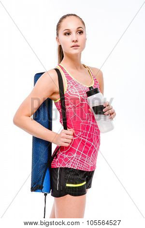 Young beautiful sportswoman in pink top and black shorts with blue yoga mat and bottle of water