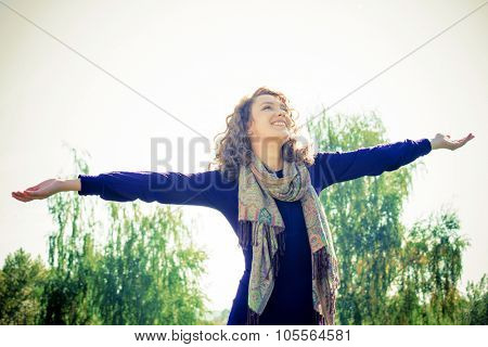 Young woman with outstretched hands enjoying outdoors