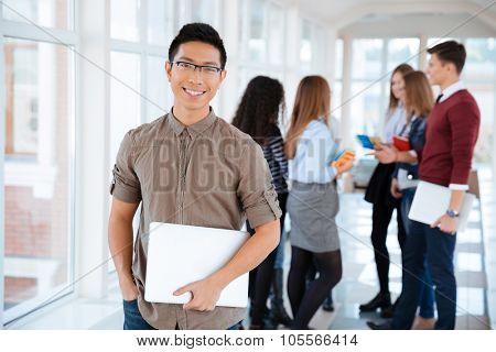 Portrait of a cheerful male student standing in university hall with classmates on background