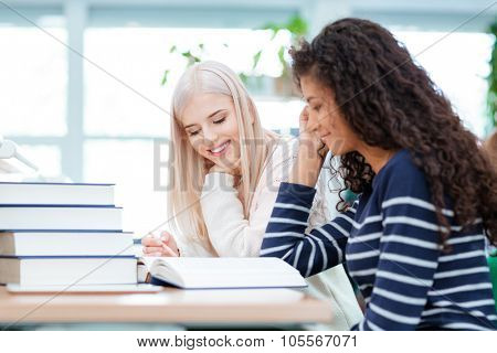 Smiling two women doing homework together in university library
