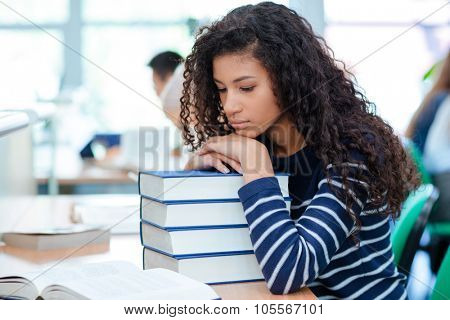 Young curly african american girl is sitting in a sad mood putting her head on books