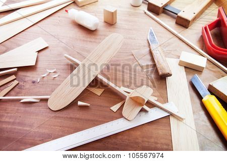 Making model airplane from wood. Wooden air plane handcrafted with balsa wood, on work table by the window. Airplane, knife, balsa wood material and glue on table.