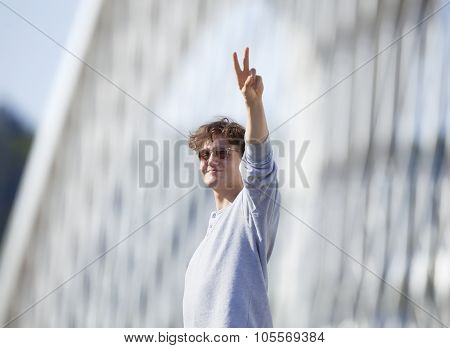 Young Man Standing On The Bridge Making V-sign