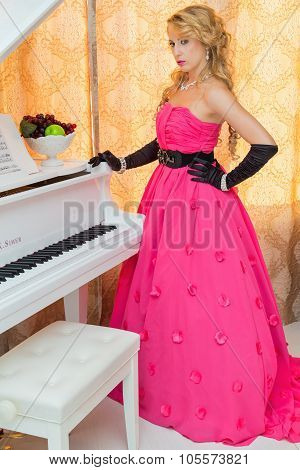 Classy Blonde In Long Red Dress Is Standing Next To The  Piano