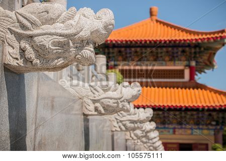 Dragon-shaped stones that adorn the walls of the walk way in a Chinese temple.