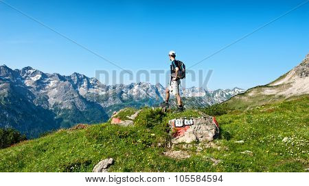 Male hiker pointing upwards in front of mountain range near Hochvogel mountain in Tyrol, Austria