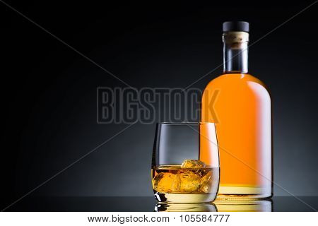 Whiskey Glass And Bottle On Black Glass Surface