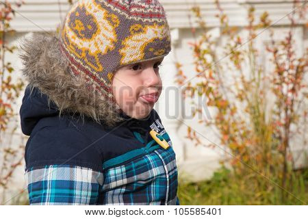 The Little Boy In A Warm Cap And A Jacket On The Street Pouted And Flicked Out Tongue Language