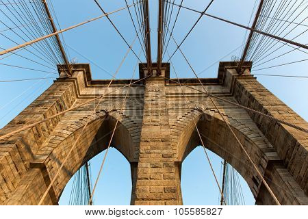 Structural detail of Brooklyn Bridge, New York, looking up one of the central stone support towers at the suspension cables in a travel and tourism concept