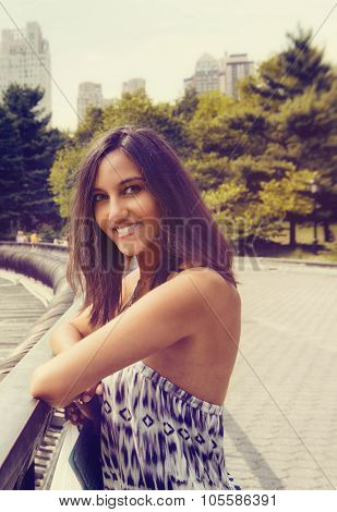 Smiling young woman in Central Park, NYC, standing leaning on the railings as she enjoys a sightseeing trip on her summer vacation