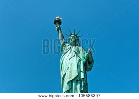 Statue of Liberty, New York harbour, USA in a frontal view against a clear blue sunny sky with lateral copyspace in a travel and tourism concept