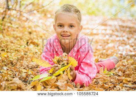 Six Year Old Girl Lying On The Yellow Fallen Leaves