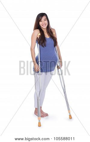 Full Length Portrait Of A Smiling Pregnant Woman Using Crutch , Isolated