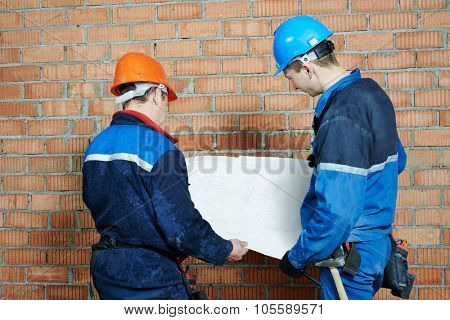 two electrician builder engineer with blue print scheme project indoors during cabling