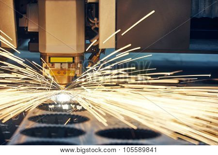 metal working. Laser cutting technology of flat sheet metal steel material processing with sparks. Authentic shooting in challenging conditions.