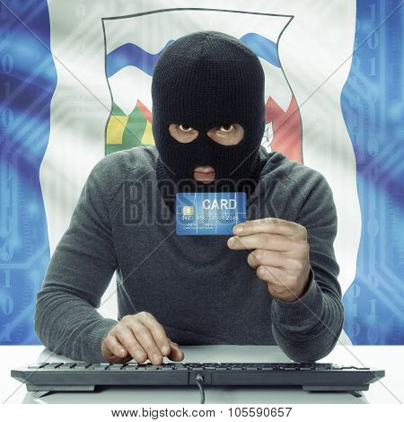 Dark-skinned Hacker With Canadian Province Flag On Background Holding Credit Card - Northwest Territ